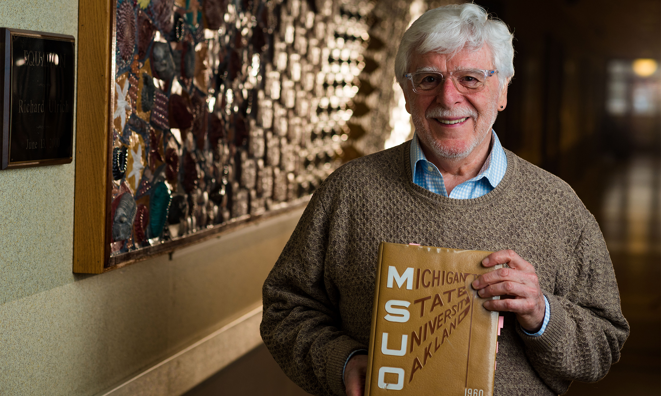 Oakland University graduate Al Monetta holds a Michigan State University Oakland yearbook