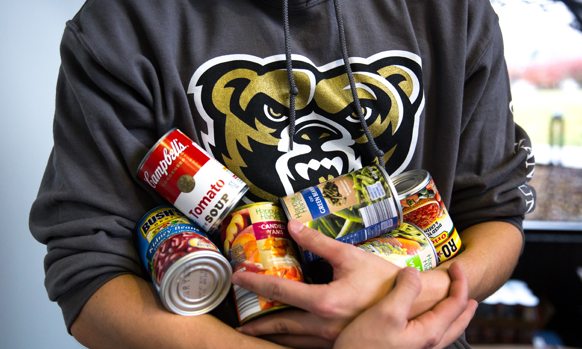 Oakland University student in gray sweatshirt with grizzly head on the front hold cans of food