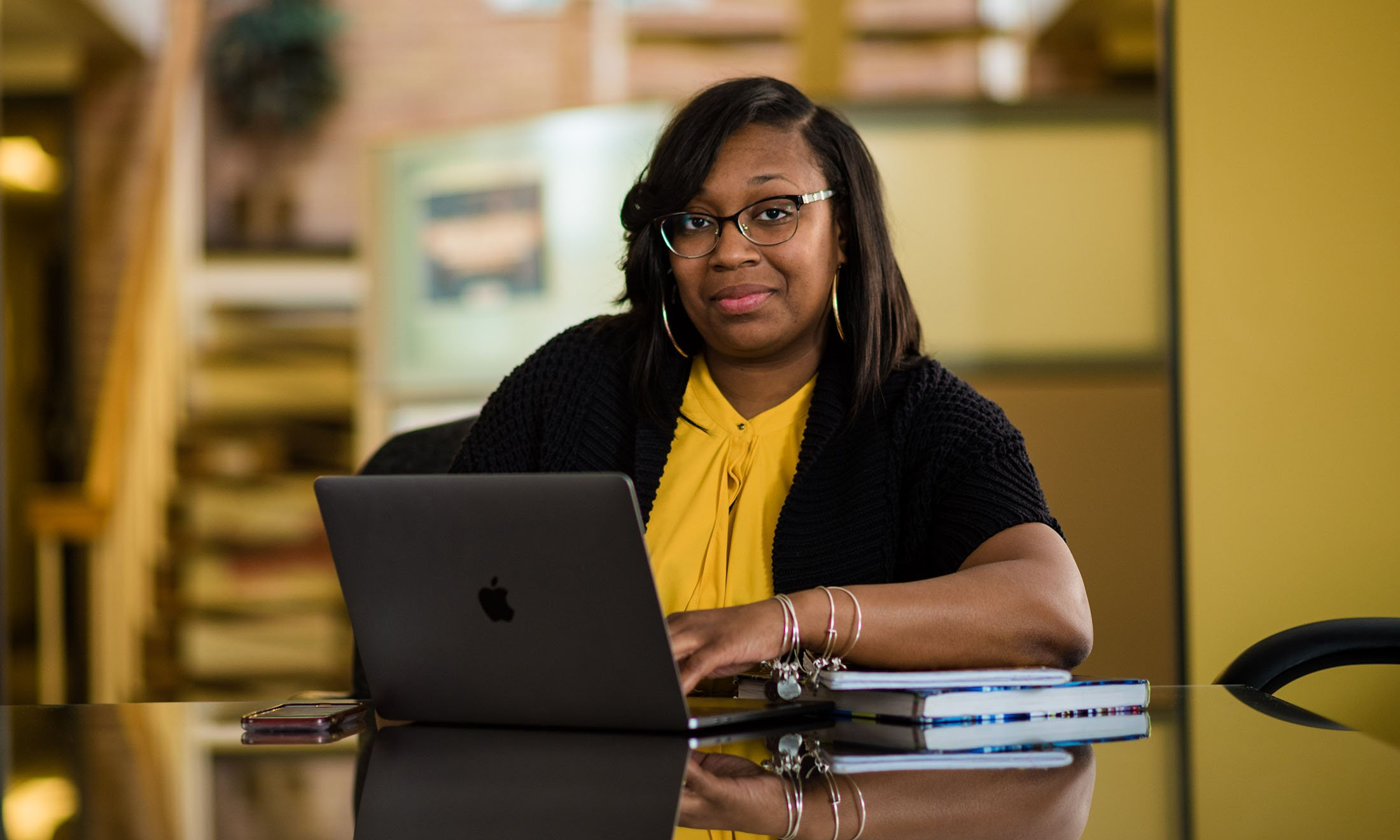 Nakisha Scruggs sits at a table on her laptop