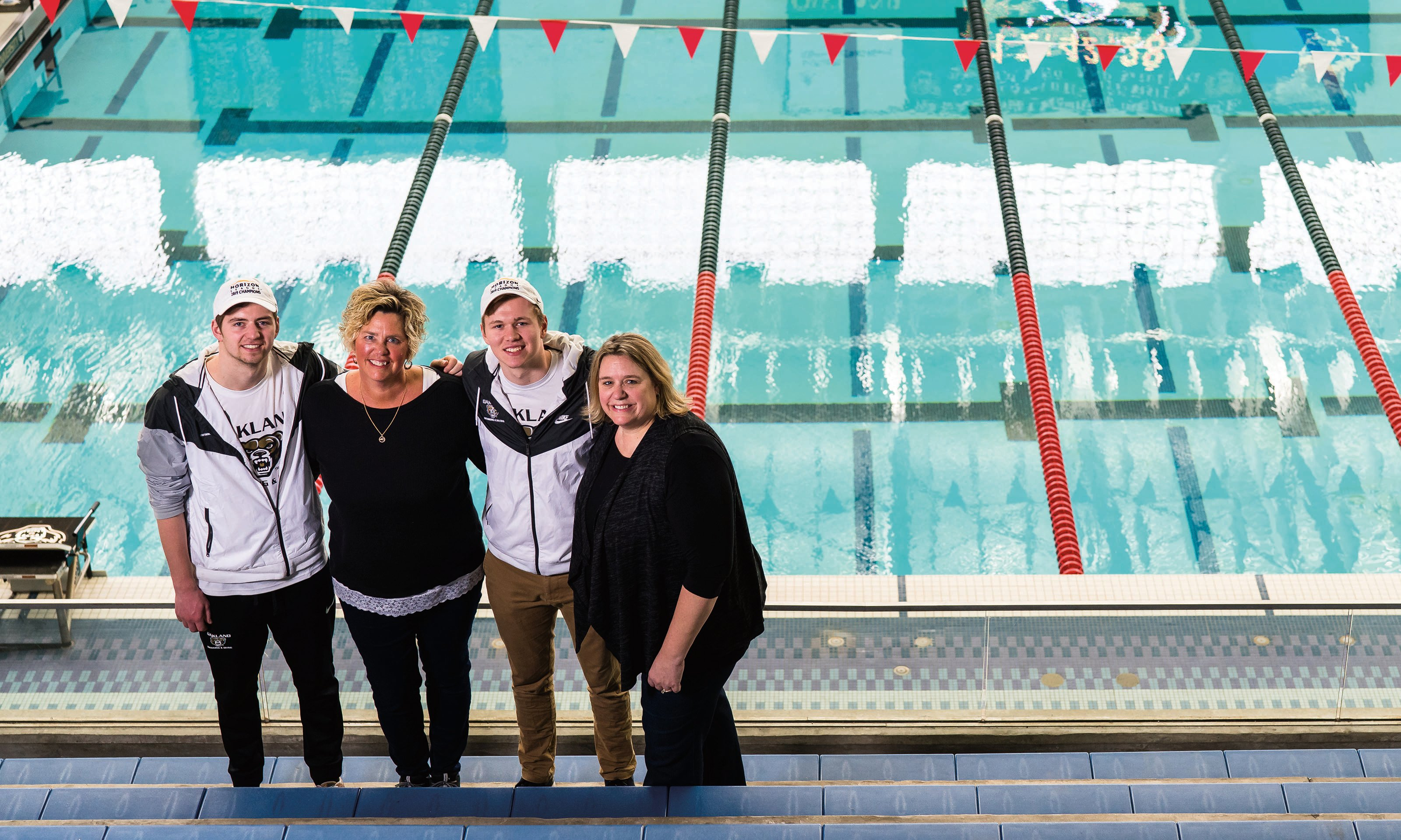 family of two sons, mom and aunt stand together smiling by swimming pool
