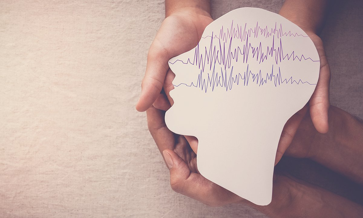 Hands holding a paper face profile with showing brain wave activity.