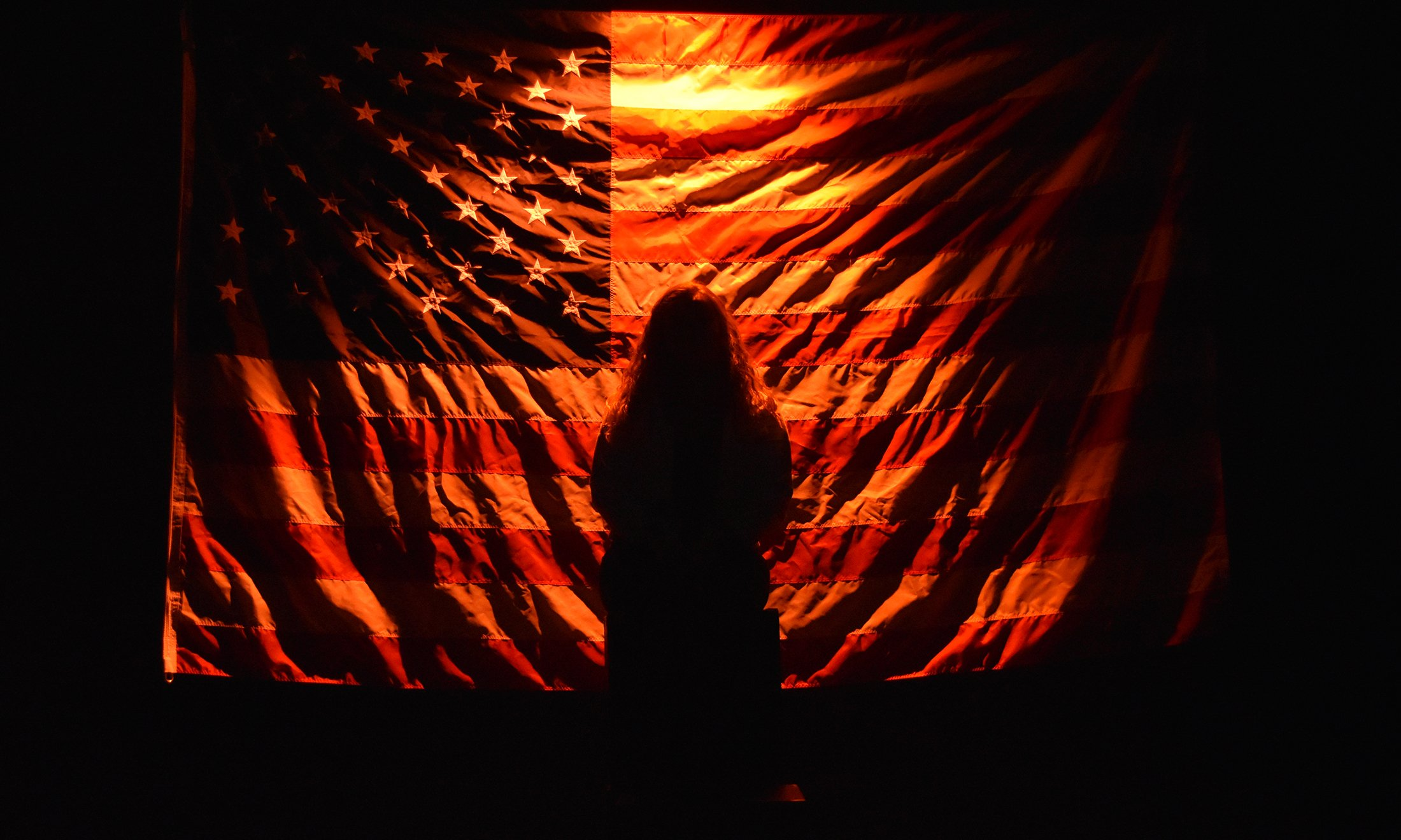 A silhouette of a person in front of the USA flag.