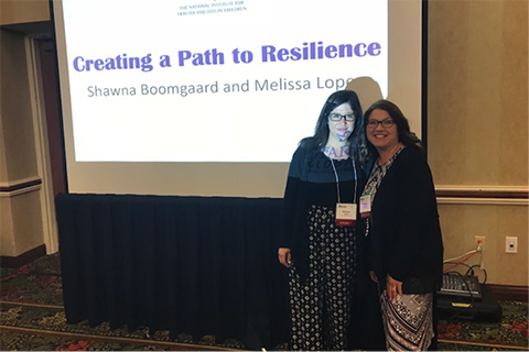 "two women in professional clothing standing in front of a projector that says ""creating a path to resilience shawna boomgaard and melissa lopez"""