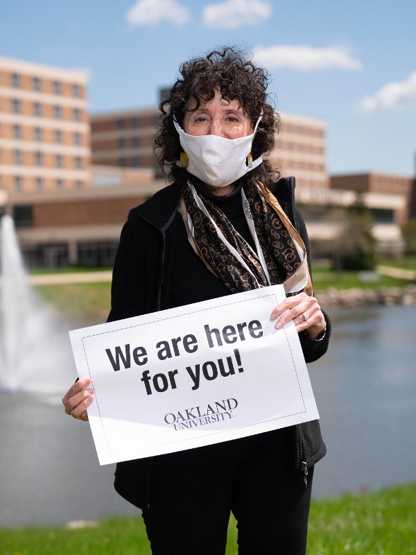 "President Ora Hirsch Pescovitz wearing a mask and holding a sign that says ""We are here for you!"""