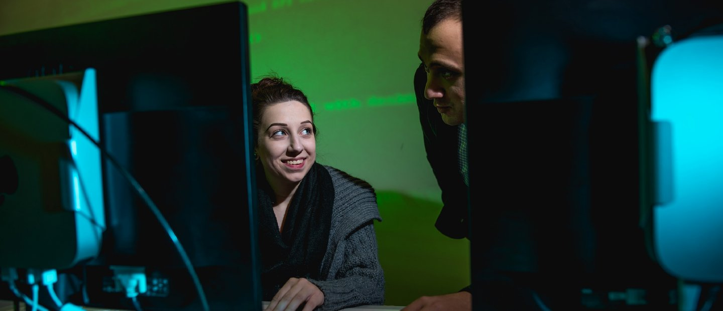student and instructor looking at a computer screen with a green wall in the background