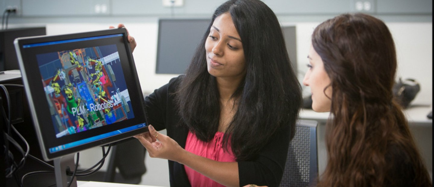 woman showing a screen with colorful images and P L M - Robotics on it to a student
