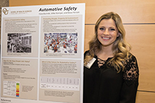 image of Ciara Bazinski standing next to her research poster