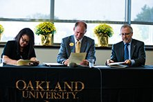 Three people seated at a table with Oakland University cloth, signing official paperwork.