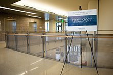 "A sign that says ""Healthology Symposium"", on a stand in an empty hallway."