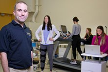 A man smiling at the camera while a woman walks on a treadmill and others perform fitness evaluations.