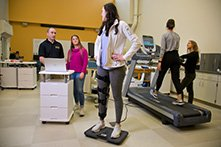A woman walking on a treadmill, another woman standing on a scale, while students perform fitness evaluations.