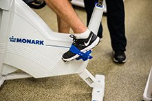 A person's foot pedaling an exercise bike.