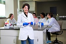 Arwa Hadid in a white lab coat and blue gloves in a Clinical and Diagnostic Sciences lab with other students seated behind her.
