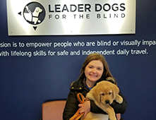 "image of Annie Fuelle holding a puppy with a ""Leader Dogs"" sign behind her"