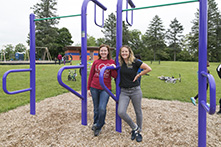 image of two girls leaning against park equipment at a park with swings and bikes in the background