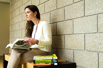 image of a woman sitting on a bench in front of a brick wall holding books