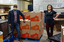 image of two OU employees standing in a warehouse-style room with big boxes and wearing masks