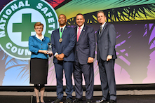 "image of four men and one woman in professional attire standing on a stage with a sign in the background reading ""National Safety Council"""