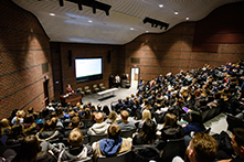 image of a lecture hall filled with people listening to a speaker
