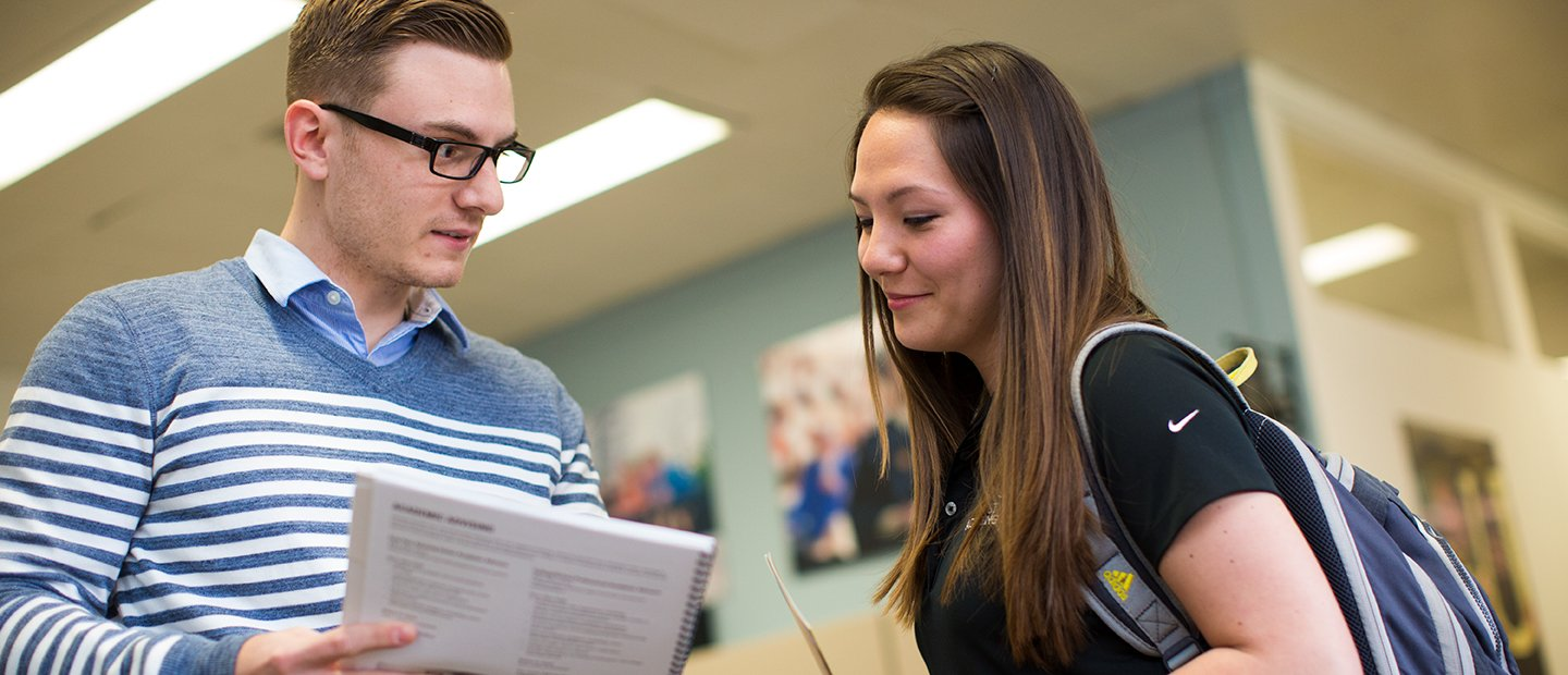 Adviser showing a booklet to a student