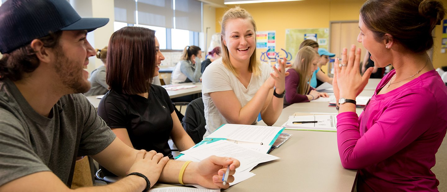 Woman talking to students in a classroom, smiling