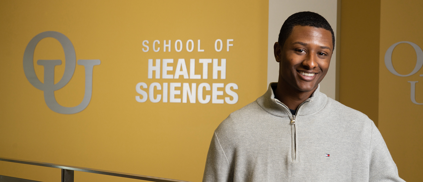 image of a student standing in the Human Health Building in front of a sign with the interlocking OU and School of Health Sciences text