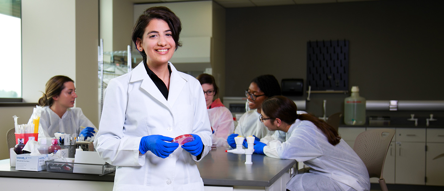 young woman in a white lab coat and blue gloves, smiling at the camera