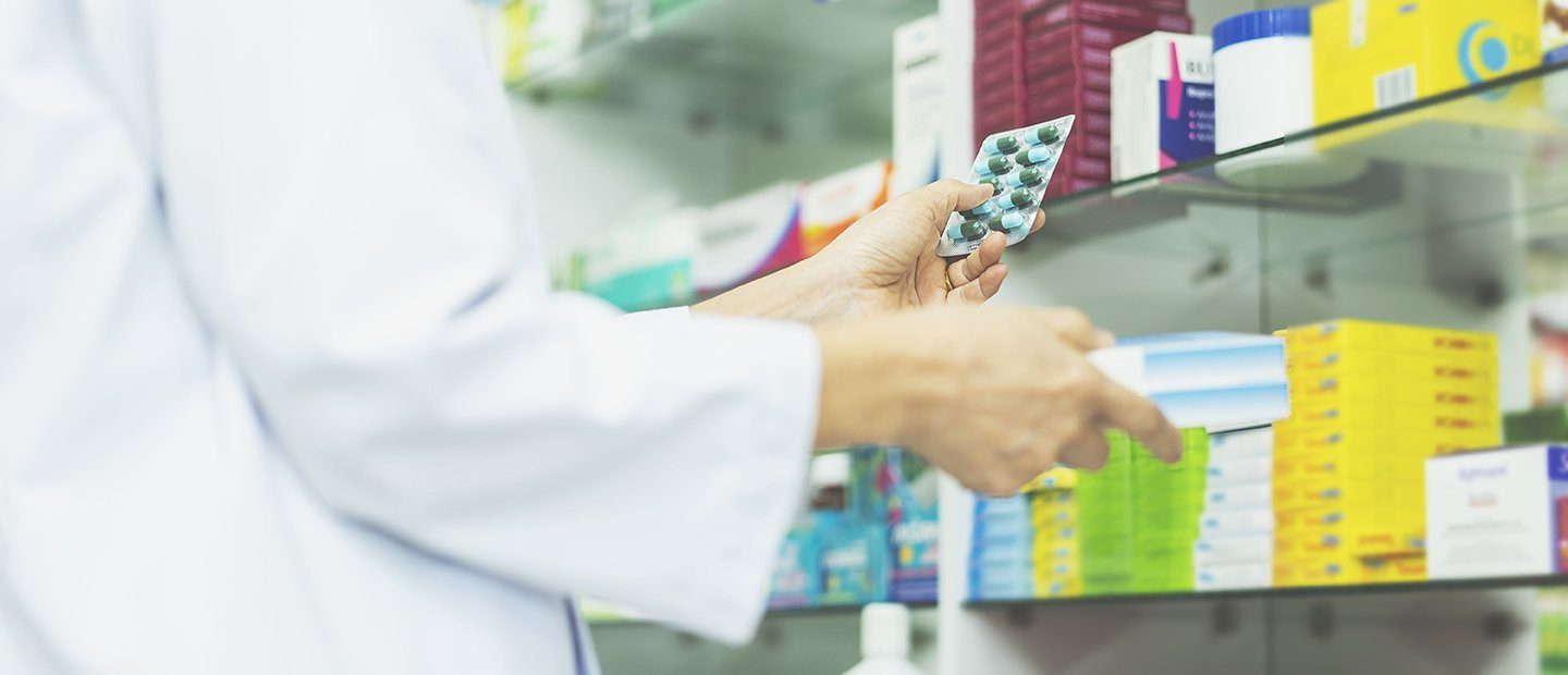 Person in a white lab coat holding a pack of pills in front of a shelf of medicine.