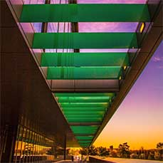 architectural detail of the engineering center showing green horizontal slots in the awning against a purple and orange sunset