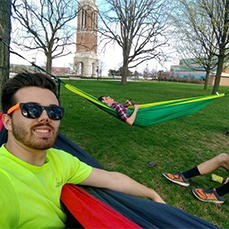 2 guys in their own hammocks and one sitting on the grass in front of Elliott Tower