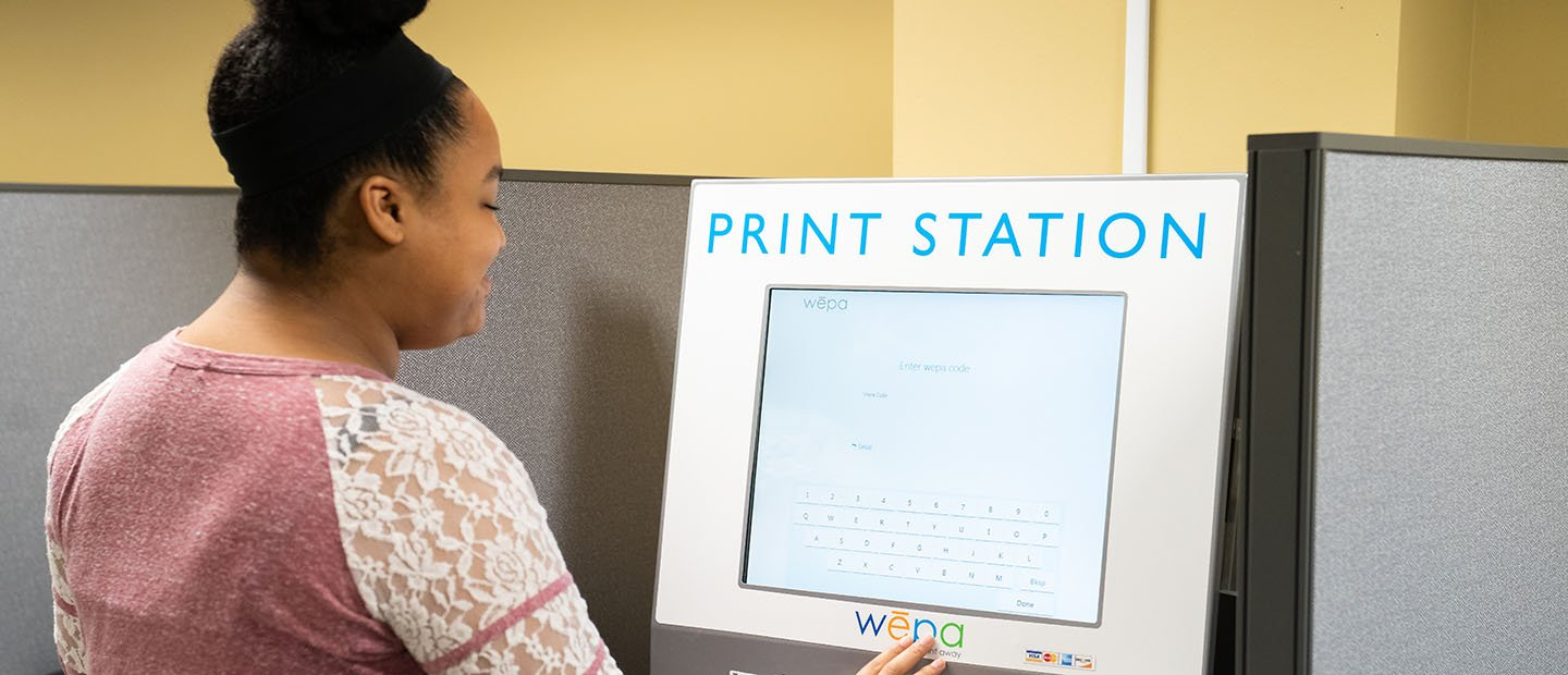 young woman standing at a computer screen on a Print Station