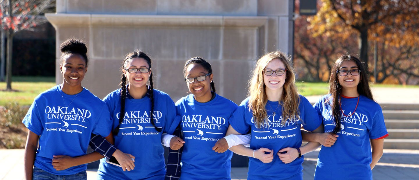 five young women in blue Oakland University shirts, standing outside with arms interlocked