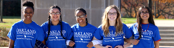 Female students linking arms, wearing blue Oakland University Second Year Experience shirts