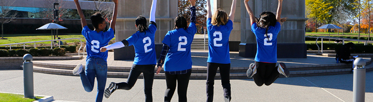 Female students jumping, wearing blue shirts with number 2 on the back