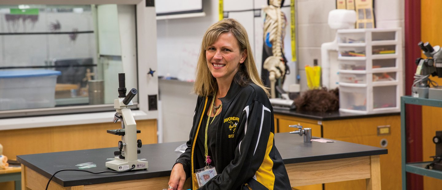 A teacher in an athletic jacket seated at a lab table with a microscope on it.