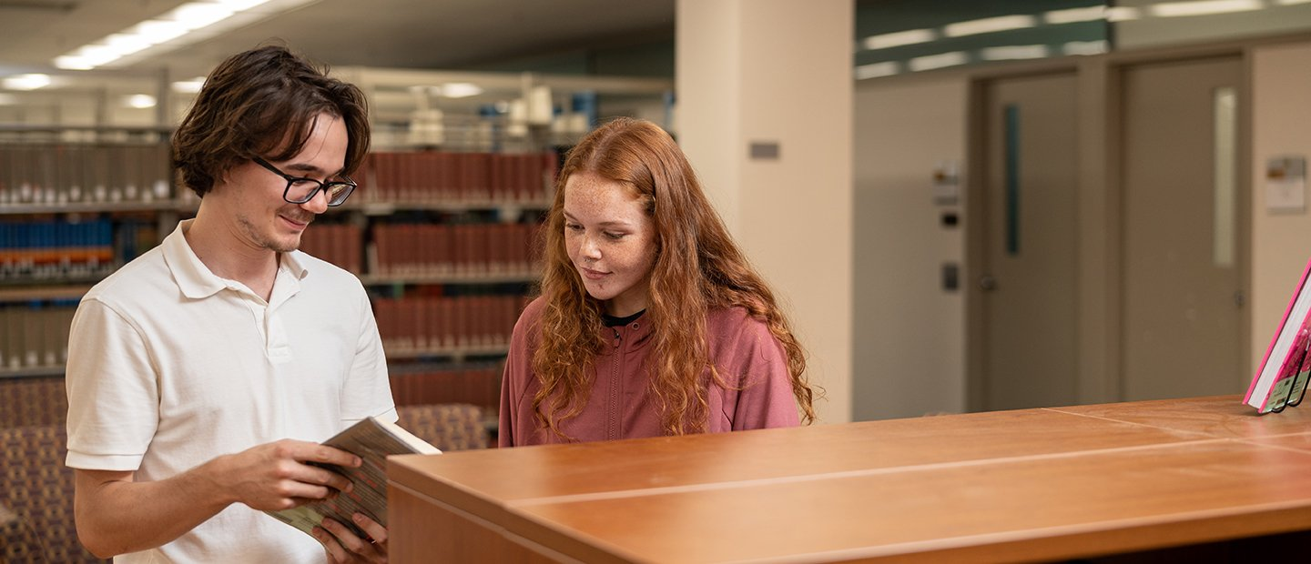 young man and woman looking at a book together in a library