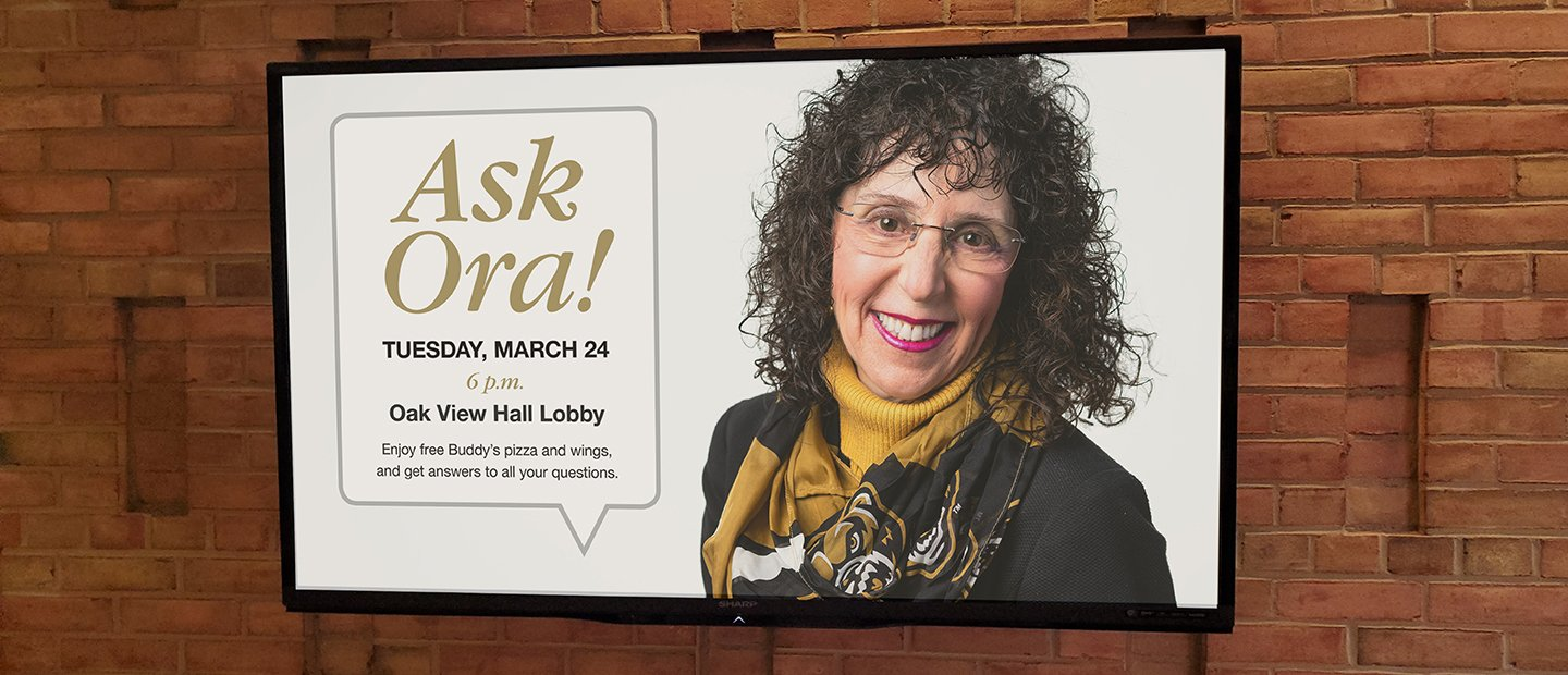 "Television screen with a photo of Ora Hirsch Pescovitz and details about an event titled ""Ask Ora!"""