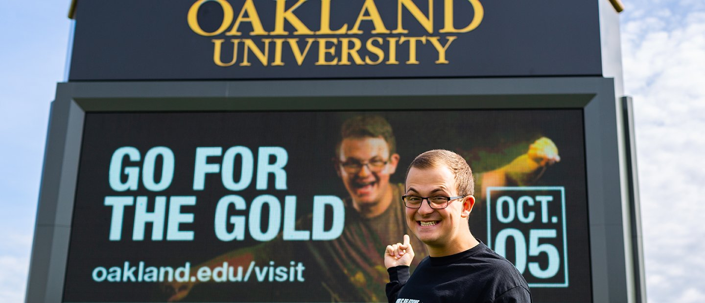 Young man pointing to an ad that he is featured in on an Oakland University electronic marquee.
