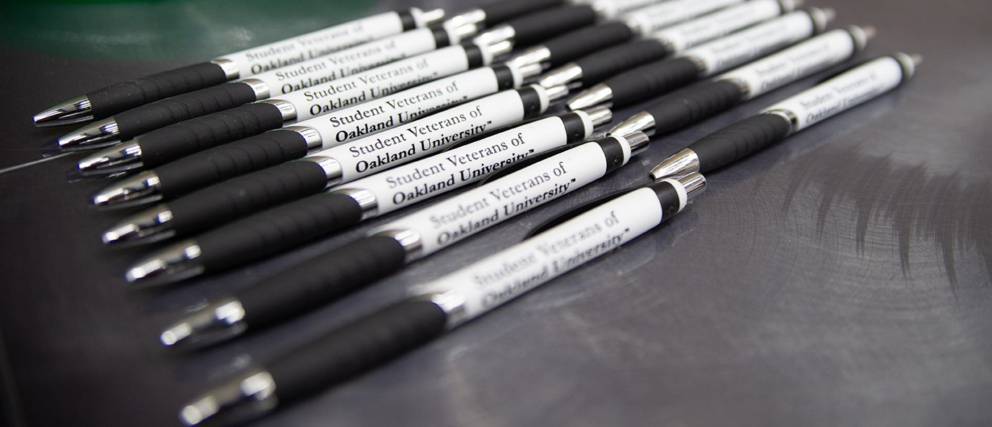 "A row of black and white ink pens that say ""Student Veterans of Oakland University"" on them."