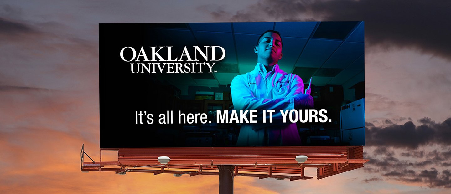 "A billboard featuring a young man and the words ""Oakland University. It's all here. Make it Yours."""