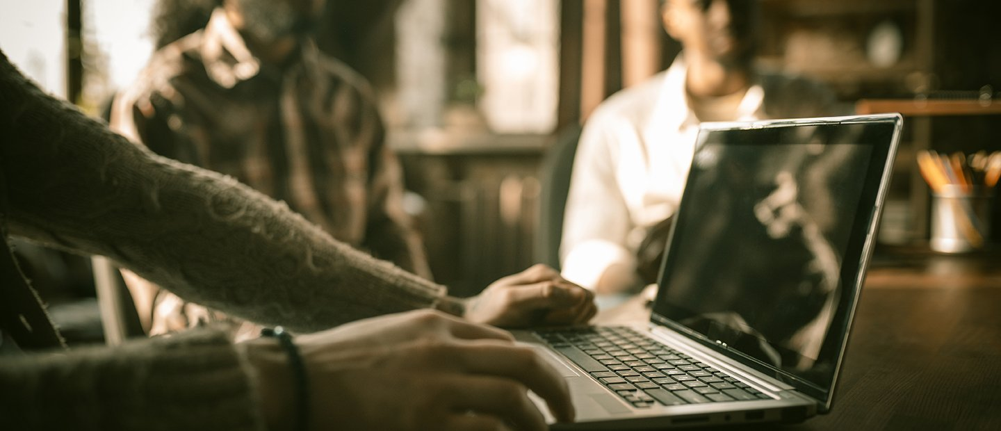 Person using a laptop at a table with two other people.