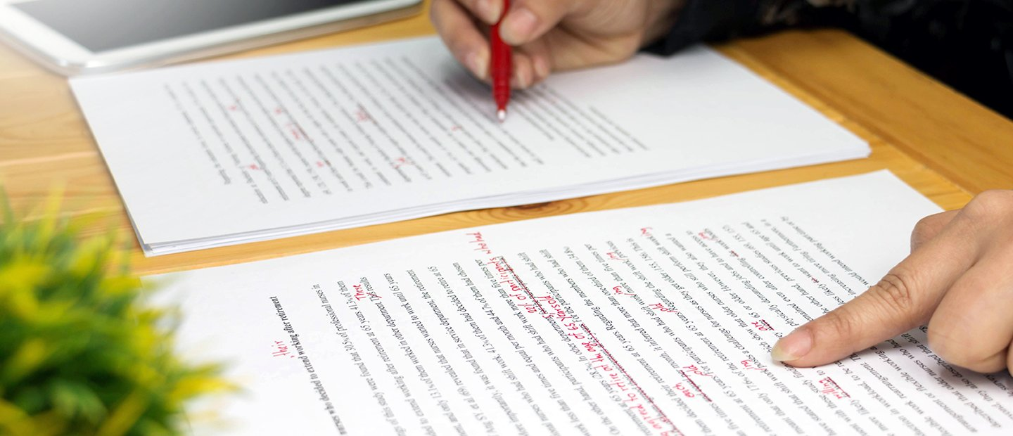 A person proof-reading a document and marking corrections in red pen.