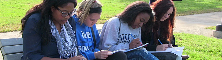 Students sitting outside on bench writing in notebooks